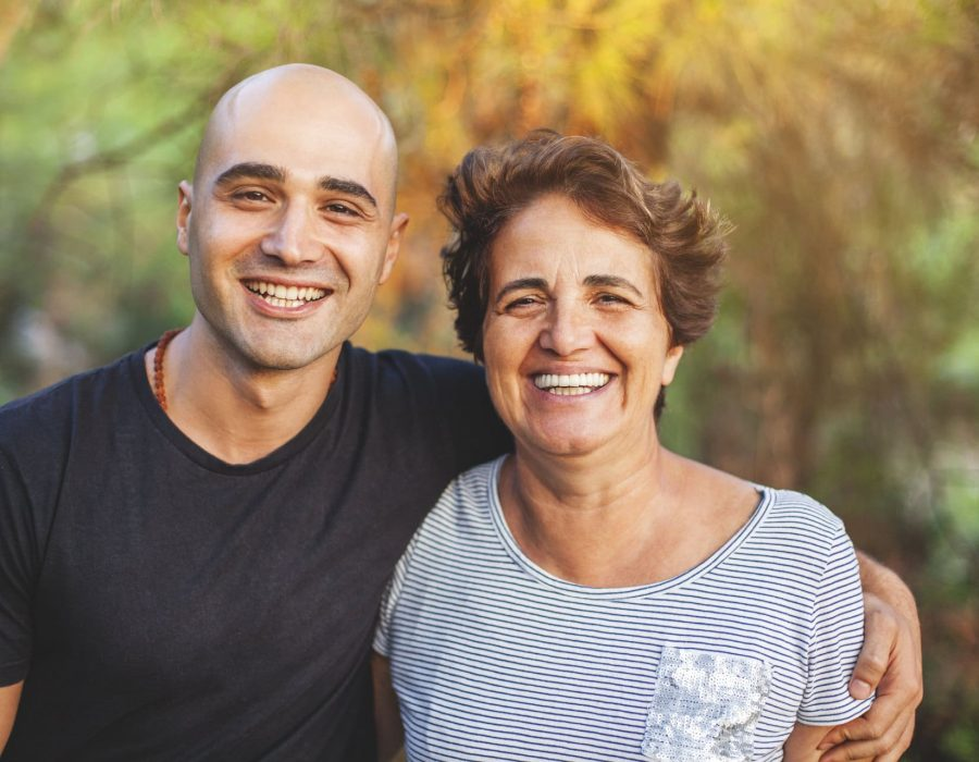 Mature mother and young son smiling at the park